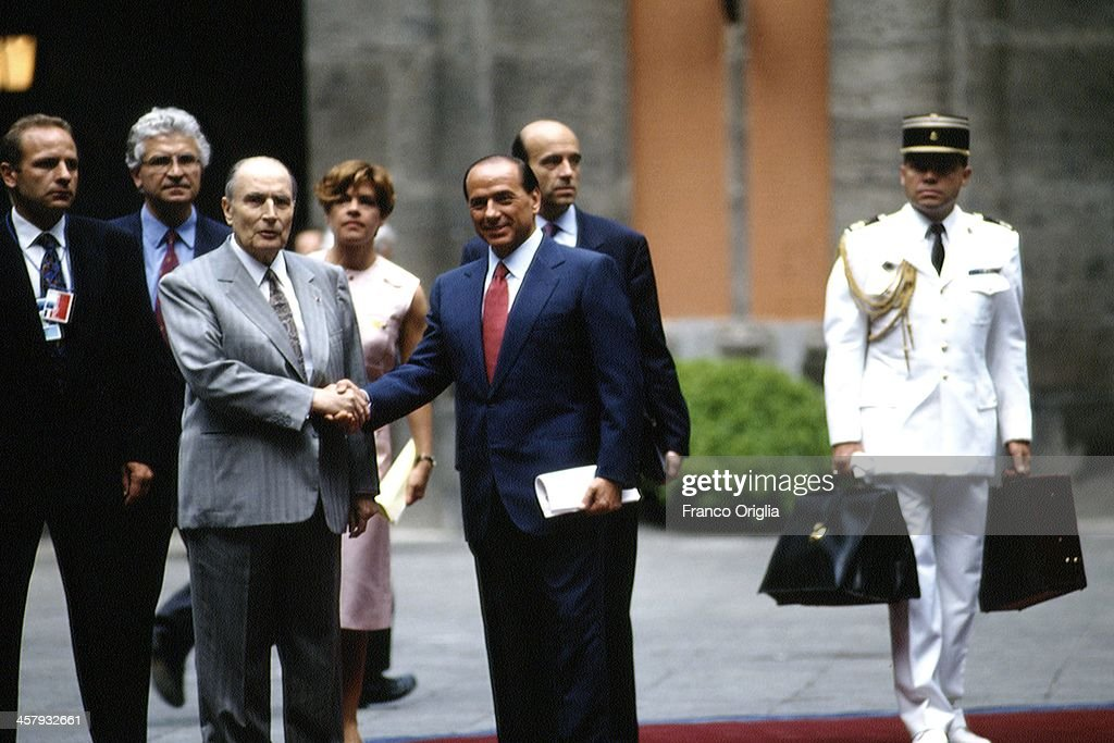 Italian Prime Minister <a gi-track='captionPersonalityLinkClicked' href=/galleries/search?phrase=Silvio+Berlusconi&family=editorial&specificpeople=201842 ng-click='$event.stopPropagation()'>Silvio Berlusconi</a> shakes hands with French President <a gi-track='captionPersonalityLinkClicked' href=/galleries/search?phrase=Francois+Mitterrand&family=editorial&specificpeople=208938 ng-click='$event.stopPropagation()'>Francois Mitterrand</a>, in the background French Foreign Minister <a gi-track='captionPersonalityLinkClicked' href=/galleries/search?phrase=Alain+Juppe&family=editorial&specificpeople=235359 ng-click='$event.stopPropagation()'>Alain Juppe</a> (R) and Mitterrand's adviser <a gi-track='captionPersonalityLinkClicked' href=/galleries/search?phrase=Anne+Lauvergeon&family=editorial&specificpeople=593162 ng-click='$event.stopPropagation()'>Anne Lauvergeon</a> during the G7 Summit at the Royal Palace of Naples, Piazza del Plebiscito, on July 9, 1994 in Naples, Italy.