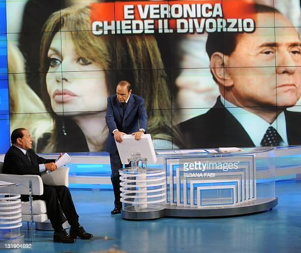 Italian Prime Minister Silvio Berlusconi speaks to TV presenter Bruno Vespa while a portrait of his wife Veronica Lario and himself is projected...