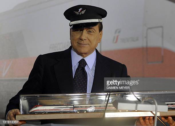 Italian Prime Minister Silvio Berlusconi wearing a train driver's cap holds a model of the high speed train Freccia Rossa after a press conference at...
