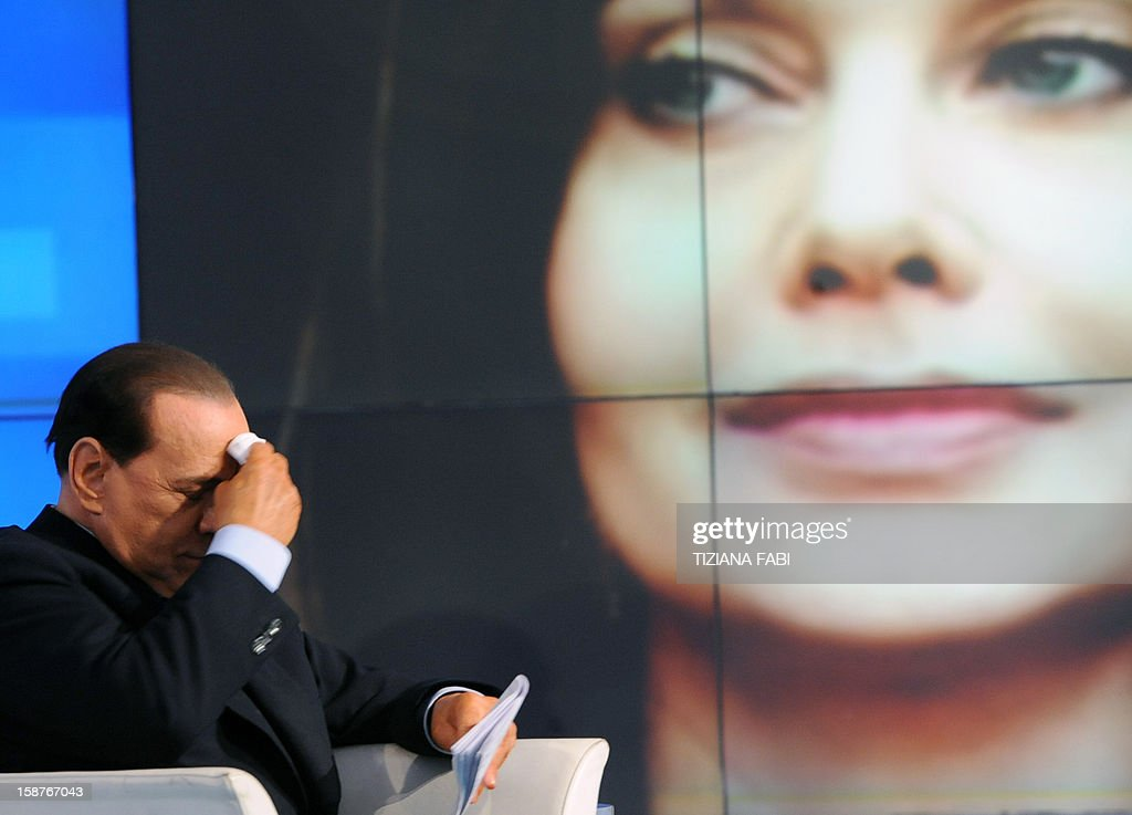 Italian Prime Minister Silvio Berlusconi wipes his brow while a portrait of his wife Veronica Lario is projected in the background, during the recording of 'Porta a Porta', a programme of Italian channel Rai 1 on May 5, 2009 in Rome. Silvio Berlusconi has been ordered by an Italian court to pay his second wife Veronica Lario three million euros ($3.95 million) a month alimony as part of a legal separation settlement which opens the way for their divorce, media reports said December 28, 2012. AFP PHOTO / TIZIANA FABI