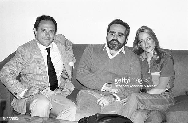 Italian publisher and entrepreneur Angelo Rizzoli and his wife Italian actress Eleonora Giorgi sitting on a couch next to Italian actor and director...