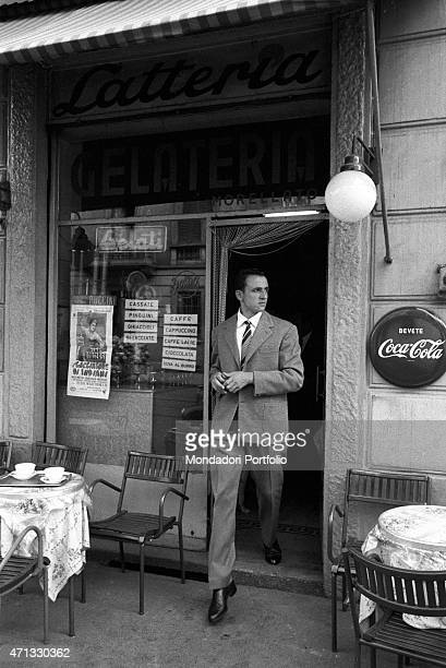 Italian racing cyclist Ercole Baldini coming out of a dairy shop before visiting the sanctuary of the Madonna del Ghisallo the cyclists' patron saint...