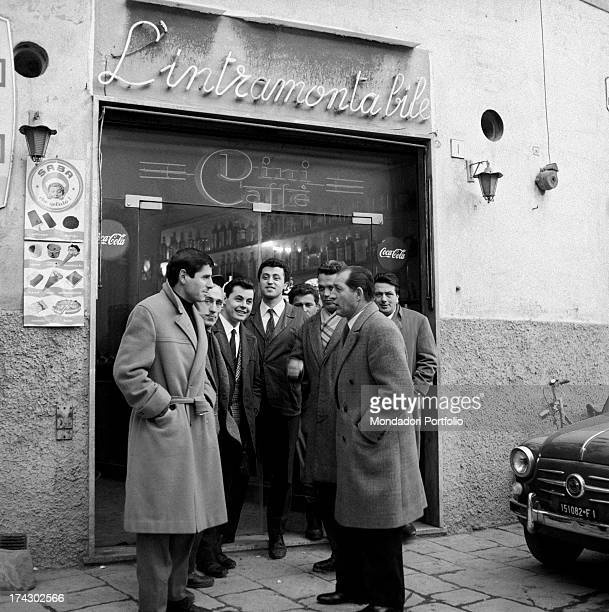 Italian racing cyclist Gino Bartali talking to some men at the entrance of the bar L'intramontabile Florence 1960s