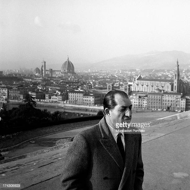 Italian racing cyclist Gino Bartali walking in the street In the background Santa Maria del Fiore cathedral with Brunelleschi's famous dome Florence...