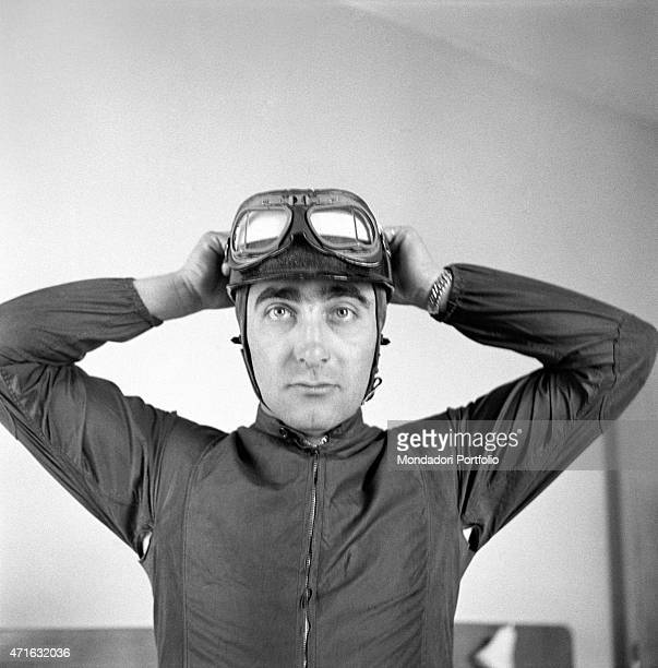 'Italian racing driver Eugenio Castellotti wearing his racing goggles waiting for taking part in the Mille Miglia Automobile Race Castellotti will...