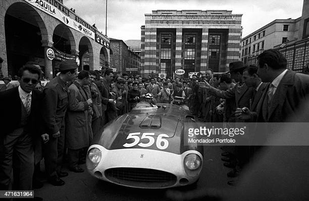 Italian racing driver Luigi Musso sitting in his Ferrari surrounded by the crowd at the Mille Miglia Automobile Race Brescia April 1956
