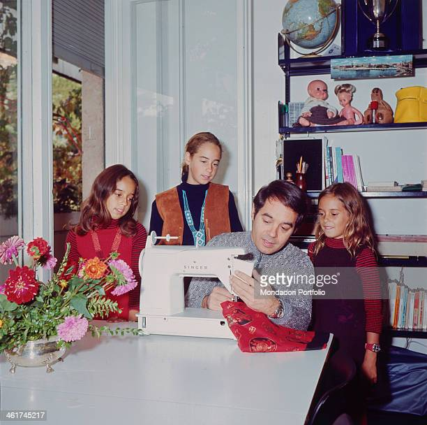 Italian radio host TV director and author Gianni Boncompagni using a sewing machine while three little girls are looking at him Italy 1971