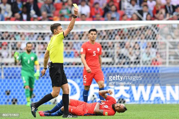 Italian referee Gianluca Rocchi gives a yellow card during the 2017 Confederations Cup group B football match between Chile and Australia at the...