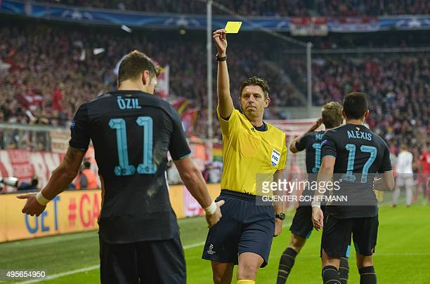 Italian Referee Gianluca Rocchi shows Arsenal's German midfielder Mesut Oezil the yellow card during the UEFA Champions League Group F secondleg...