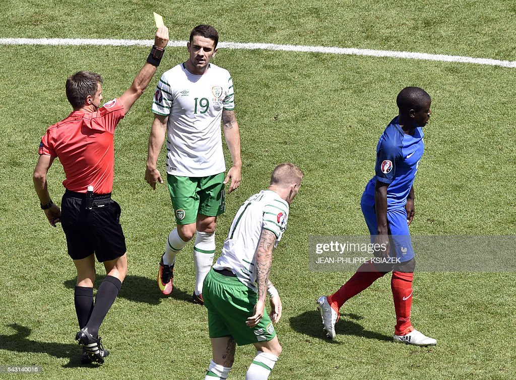 Italian referee Nicola Rizzoli (L) shows a yellow card to France's midfielder N'Golo Kante (R) during the Euro 2016 round of 16 football match between France and Republic of Ireland at the Parc Olympique Lyonnais stadium in Décines-Charpieu, near Lyon, on June 26, 2016. / AFP / JEAN