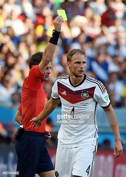 Italian referee Nicola Rizzoli shows a yellow card to Germany's defender Benedikt Hoewedes during the final football match between Germany and...