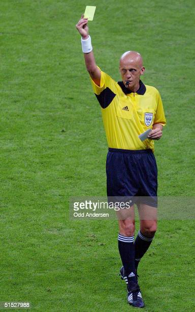 Italian referee Pierluigi Collina gives a yellow card during the Group F first round match Argentina/England of the 2002 FIFA World Cup in Korea and...