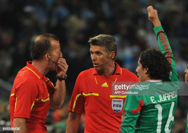 Italian referee Roberto Rosetti and assistant referee Stefano Ayroldi speak as Mexico's players argue that Argentina's striker Carlos Tevez's goal...