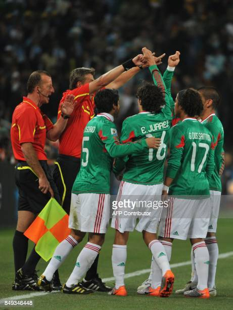 Italian referee Roberto Rosetti and assistant referee Stefano Ayroldi gesture to Mexico's players who argue that Argentina's striker Carlos Tevez's...