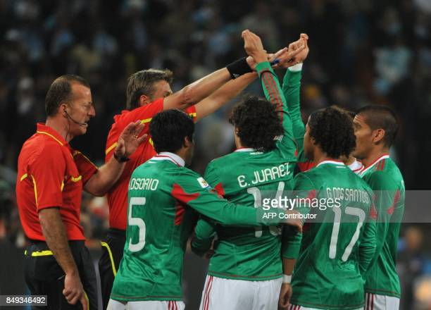 Italian referee Roberto Rosetti and assistant referee Stefano Ayroldi gesture to Mexican players who argue that Argentina's striker Carlos Tevez's...