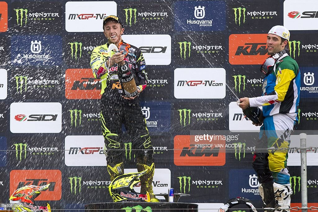 Italian rider Antonio Cairoli (L) and British rider Shaun Simpson celebrate on the podium after competing in the motocross MXGP Belgian Grand Prix, on August 3, 2014, in Lommel. AFP PHOTO / BELGA / KRISTOF VAN ACCOM **Belgium Out**