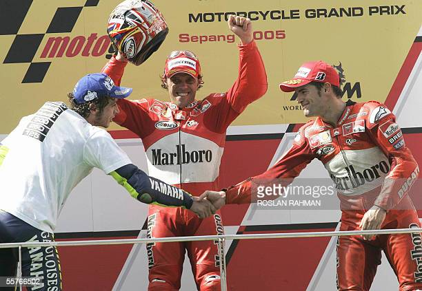 Italian rider Loris Capirossi of Ducati jubilates while his compatriot Valentino Rossi of Yamaha shakes hands with Spanish rider Carlos Checa after...