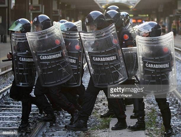 Italian riot police men cross railway tracks at the central station after protestors sat on the lines on July 7 2009 in Rome Italy Protests and...