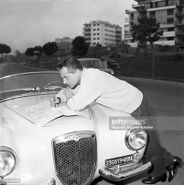 Italian Rossano Brazzi posing with his Lancia checking a map Italy 1956