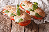 Italian sandwiches with fresh tomatoes, mozzarella cheese and basil close-up on the table. horizontal