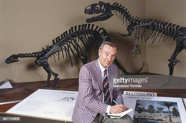 Italian science journalist and presenter Piero Angela taking note on a notebook sitting in front of the copy of the skeletons of two dinosaurs a...