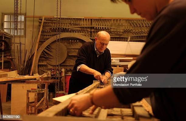 Italian sculptor Arnaldo Pomodoro creating the mold for one of his works in his atelier in Milan near the Navigli Milan 19th June 2002