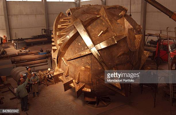 Italian sculptor Arnaldo Pomodoro with some coworkers observing the Grande Sfera being created for the Exhibition in the PalaisRoyal gardens in Paris...