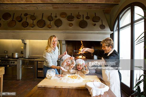 Italian shoe designer Alberto Moretti's wife Vanessa and daughters Fiamma and Albertina are photographed in the kitchen with family cook Paola...