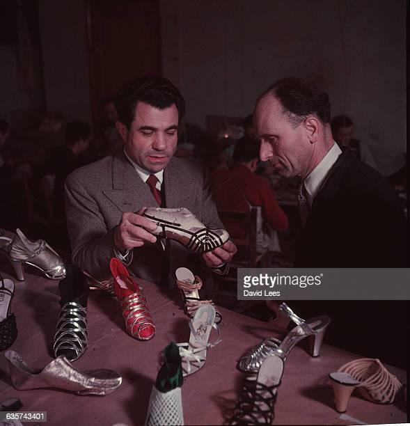 Italian shoe designer Salvatore Ferragamo discussing a selection of his shoes