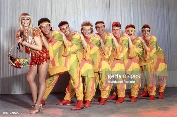 Italian showgirl and TV presenter Raffaella Carrà holding a fruit basket wearing a stage costume in the talk show Pronto Raffaella Behind her a row...