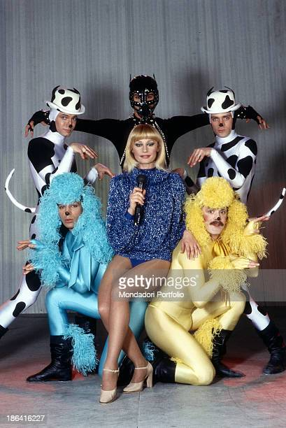 Italian showgirl Raffaella Carrà posing with some dancers in stage costume 1983