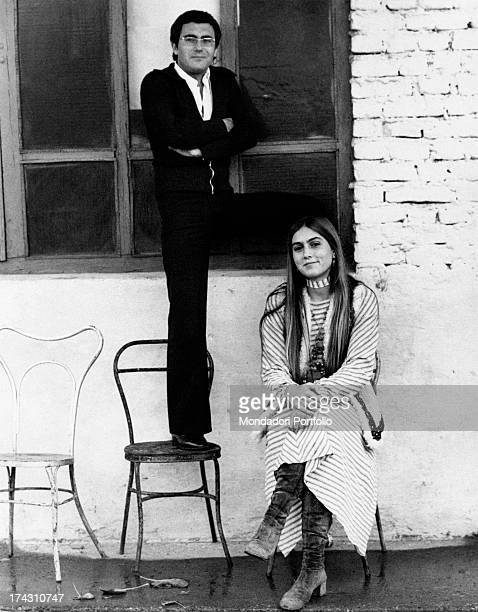 Italian singer Al Bano standing on a chair and posing with his wife Americanborn Italian singer Romina Power Milan 1970s