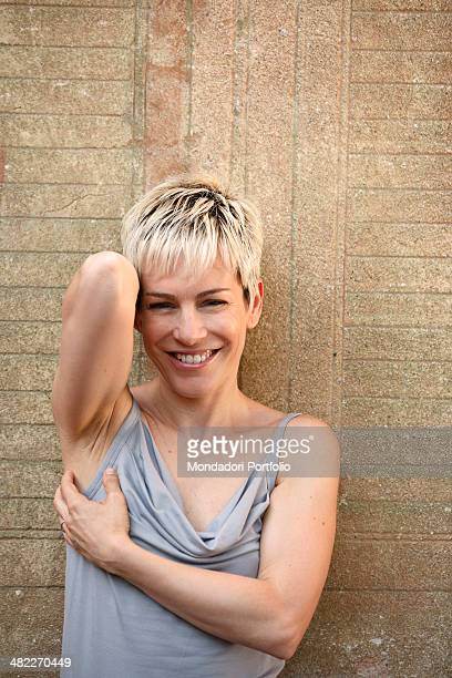 Italian singer Alexia born Alessia Aquilani smiles at the camera while posing on the background of a green window painted on a wall during a holiday...