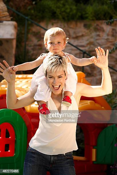 Italian singer Alexia with her daughter Maria Vittoria on her shoulders lifting up the arms of her baby girl in an amused attitude smiling at the...