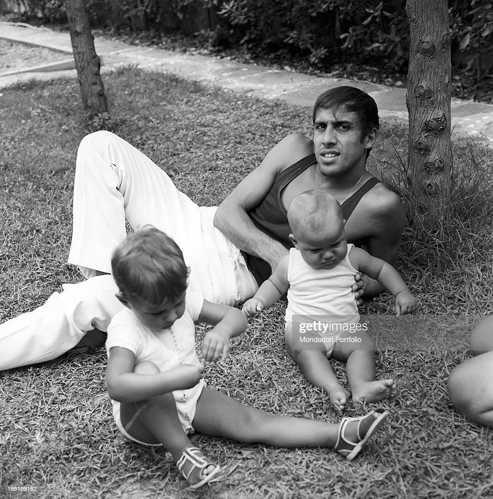 Italian singer and actor Adriano Celentano lying on a meadow with his children Rosita and Giacomo Celentano Le Focette August 1967