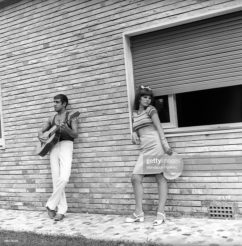 Italian singer and actor Adriano Celentano playing the guitar near his wife Italian actress Claudia Mori Le Focette August 1967