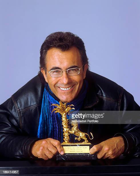 Italian singer and actor Al Bano posing smiling with the statuette of the Sanremo Music Festival Sanremo 1996