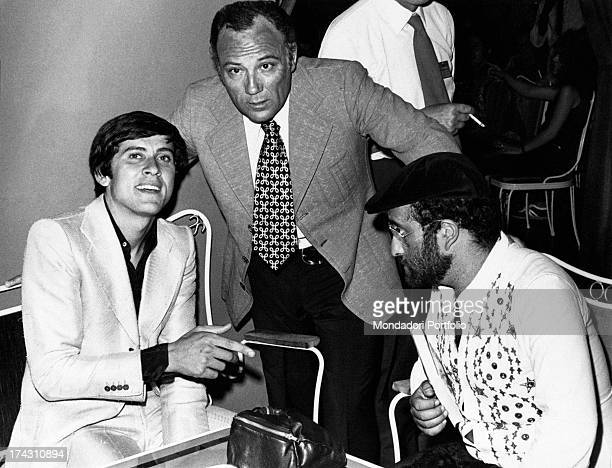 Italian singer and actor Claudio Villa talking with Italian singers Lucio Dalla and Gianni Morandi before performing at Cantagiro Recoaro Terme 1972