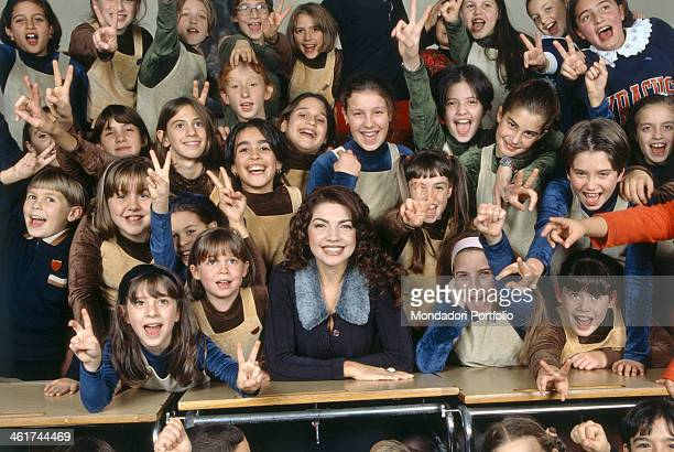 Italian singer and actress Cristina D'Avena smiles sitting on a classroom desk surrounded by a lot of kids joyfully shouting and doing the victory...