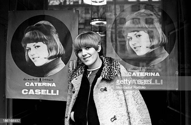 Italian singer and record producer Caterina Caselli smiling in front of the poster of her concert Turin February 1966