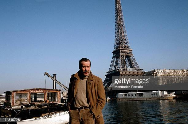 Italian singer and songwriter Paolo Conte posing posing on the bank of river Seine with the Eiffel Tower in the background Paris 1988