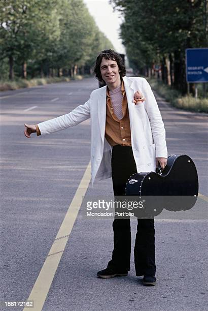 Italian singer and songwriter Rino Gaetano hitchhiking on the roadside holding a guitar case 1978