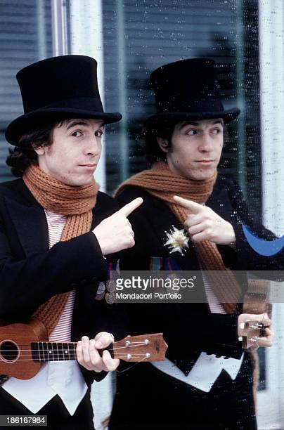 Italian singer and songwriter Rino Gaetano pointing at his mirror image wearing a tailcoat and holding an ukulele 1978