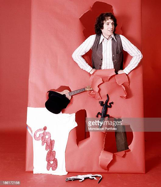 Italian singer and songwriter Rino Gaetano posing on a photo set with an ukulele a top hat and some alligators 1978