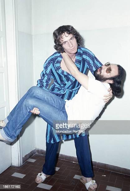 Italian singer and songwriter Rino Gaetano raising Italian singer and songwriter Antonello Venditti at Vota la voce music festival 1978