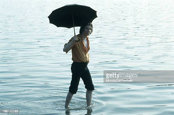 Italian singer and songwriter Rino Gaetano walking in the water with an open umbrella 1978