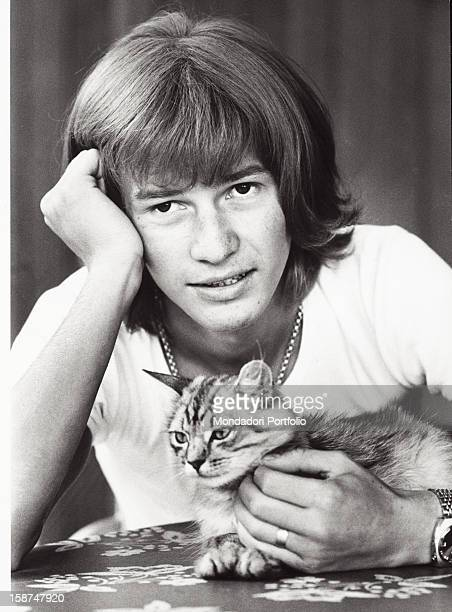 Italian singer and songwriter Ron caressing his cat Garlasco 1970s
