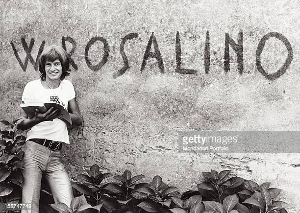 Italian singer and songwriter Ron holding a book and posing Behind him a graffiti on the wall saying W Rosalino Garlasco 1970s