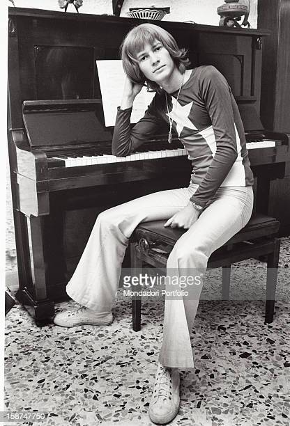 Italian singer and songwriter Ron leaning on a piano and posing Garlasco 1970s