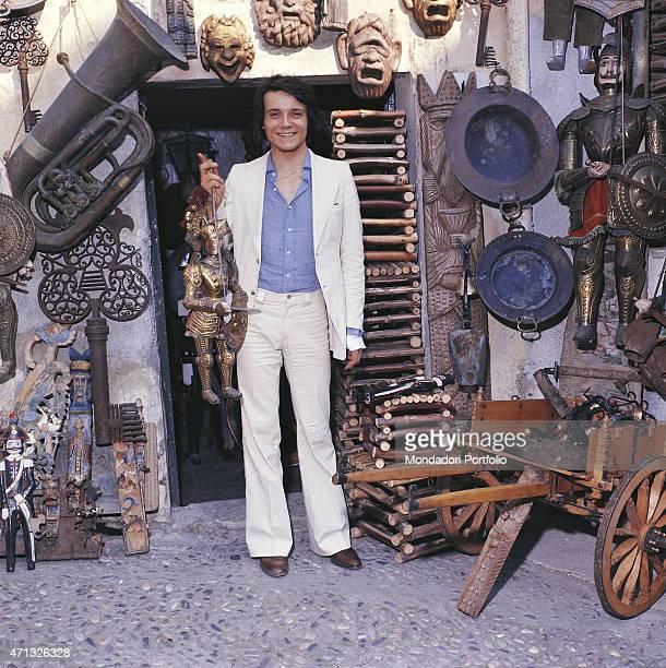 Italian singer and theatre actor Massimo Ranieri phot shooted at the entrance of a junk shop Italy 1974